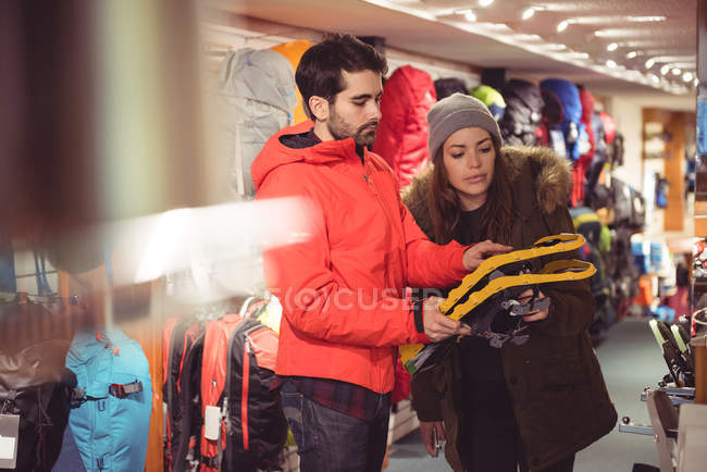 Couple selecting snowshoes together in a shop — Stock Photo