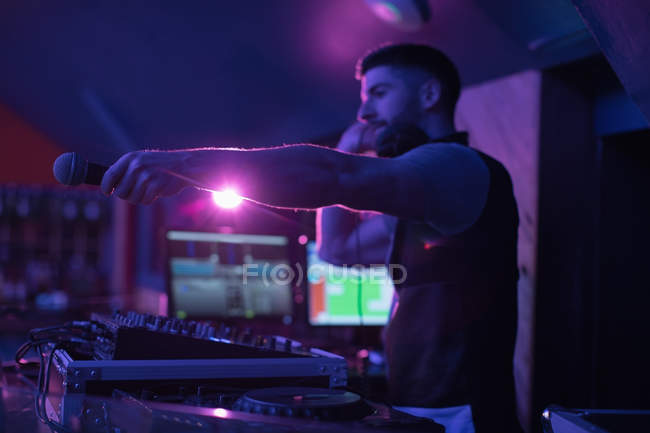 Male dj holding microphone while playing music in bar — Stock Photo