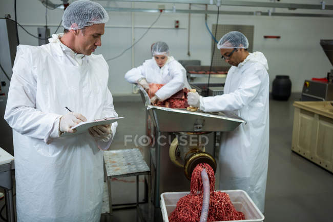 Butchers placing meat in mincing machine at meat factory — Stock Photo