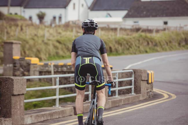 Задній вид спортсмена велосипед їзда на дорозі — стокове фото