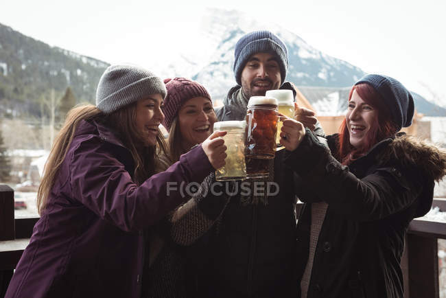 Happy friends toasting with beer glasses in bar — Stock Photo