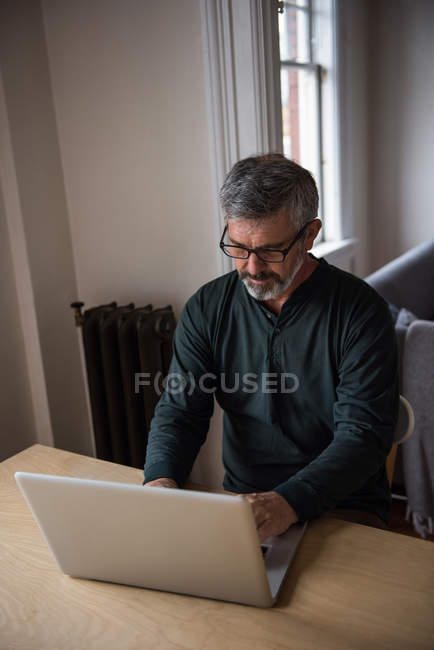 Man sitting at table and using laptop at home — Stockfoto
