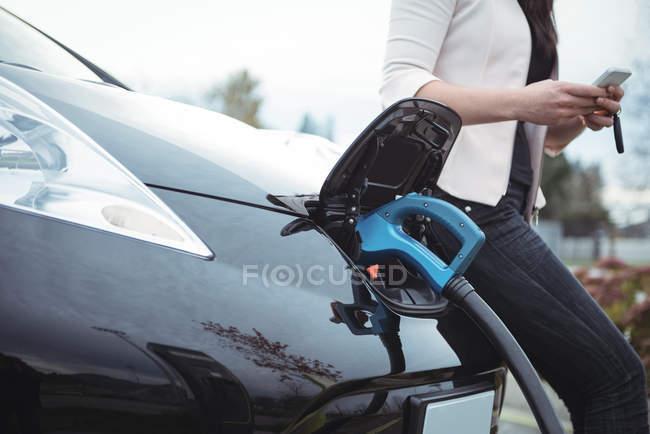Partie médiane de la femme utilisant un téléphone portable tout en rechargeant la voiture électrique dans la rue — Photo de stock