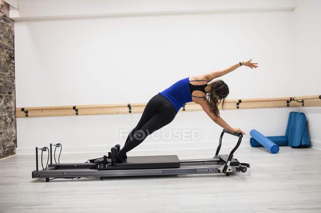 Vista posteriore della donna che si esercita sulla riformatore nello studio fitness — Foto stock