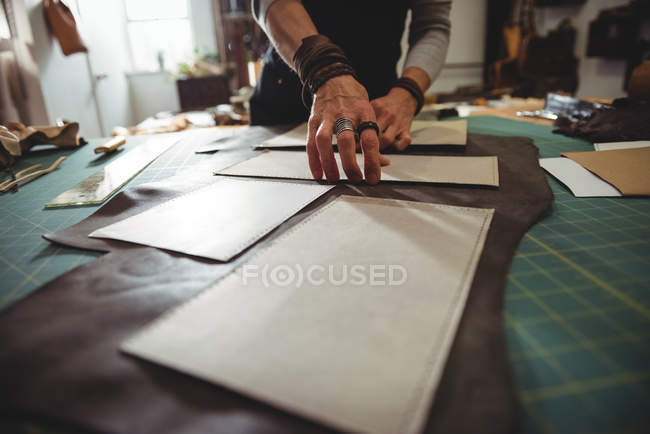 Mid-section of craftswoman arranging leather piece on work table in workshop — Stock Photo