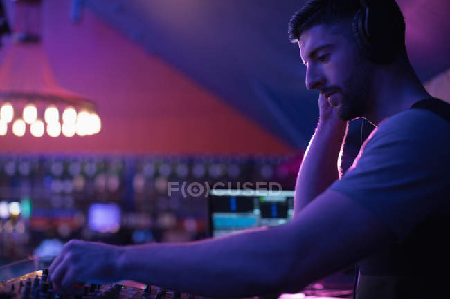 Male dj listening to headphones while playing music in bar — Stock Photo