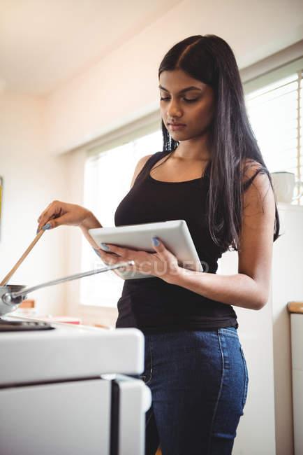 Donna che cucina e utilizza tablet digitale in cucina — Foto stock