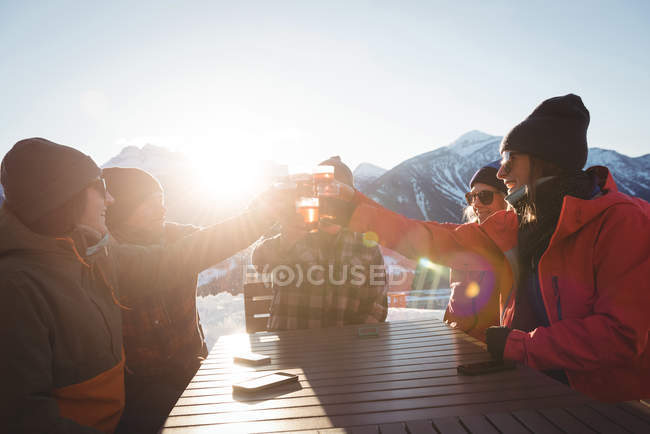 Skiers friends toasting glasses of beer in ski resort on a bright sunlight — Stock Photo