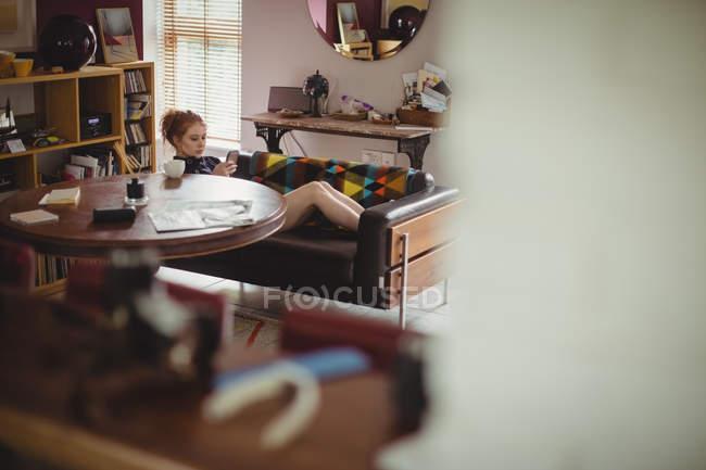 Schöne Frau mit Handy zu Hause — Stockfoto