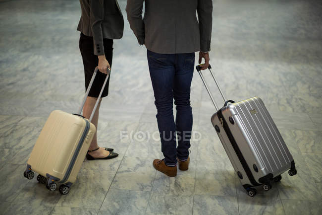 Low section of business people walking with luggage at airport terminal — Stock Photo
