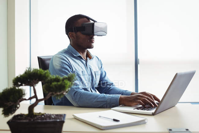 Business executive using virtual reality headset and working on laptop in office — Stock Photo
