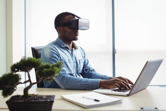 Ejecutivo de negocios con casco de realidad virtual y trabajando en equipo portátil en la oficina - foto de stock