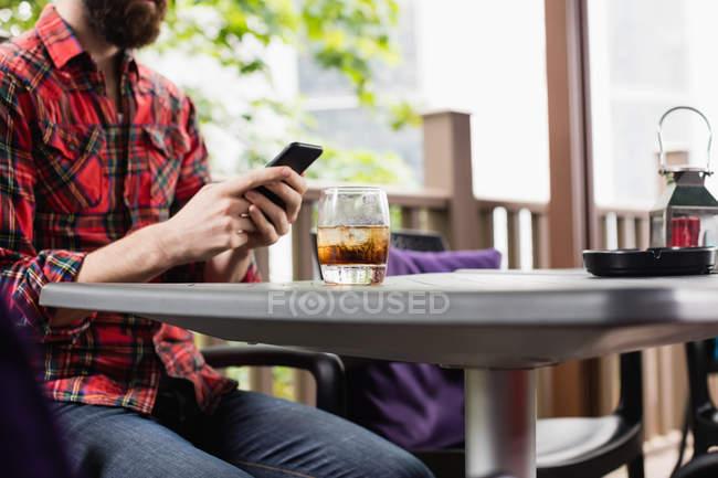 Средняя часть человека с помощью мобильного телефона, сидя в баре — стоковое фото