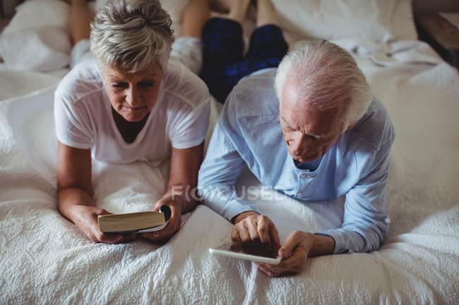 Coppia anziana con tablet digitale e libro di lettura sul letto in camera da letto — Foto stock