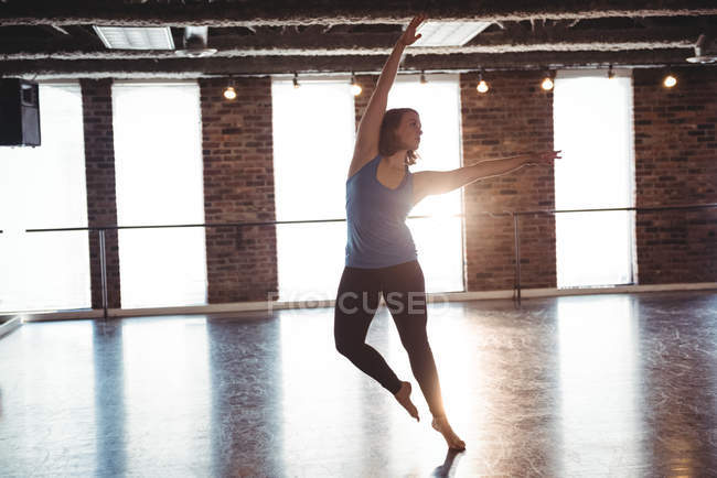 Young woman practicing modern dance in dance studio — Stock Photo
