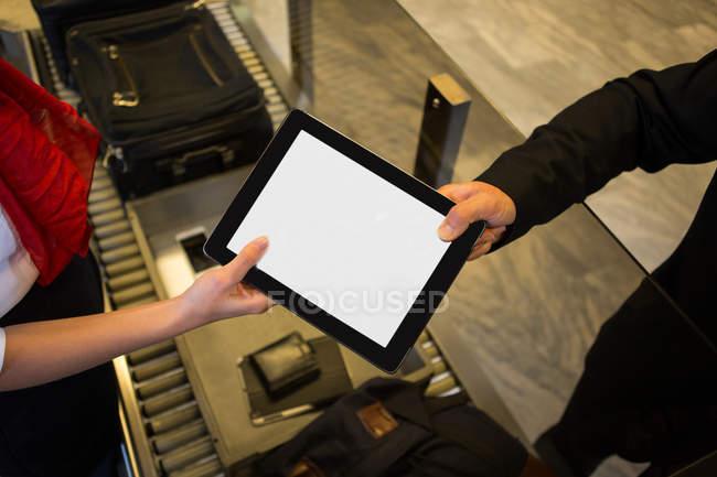 Close-up de funcionários do sexo femininos dando tablet digital ao passageiro — Fotografia de Stock