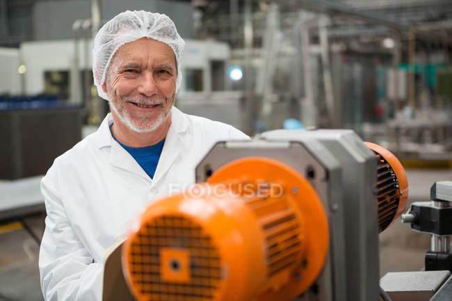 Портрет счастливого работника мужского пола, стоящего у машин на заводе холодных напитков — стоковое фото