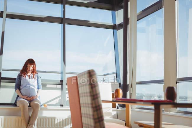 Задумчивая беременная женщина сидит у окна в гостиной дома — стоковое фото