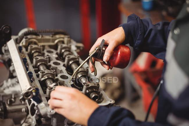 Sección media de piezas de automóviles de engrase mecánico femenino en el garaje de reparación - foto de stock