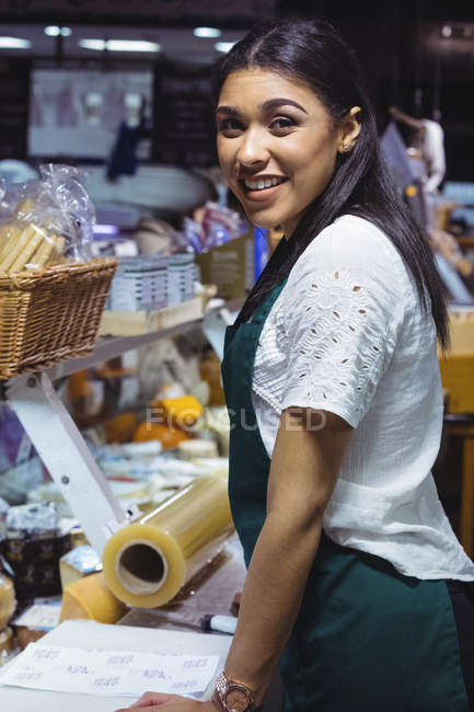 Portrait of smiling waitress standing at counter in cafe — Stock Photo