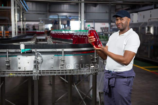 Портрет молодого рабочего, осматривающего бутылку сока на заводе — стоковое фото