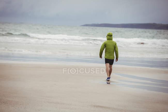 Задній вид спортсмена працює на пляжі — стокове фото