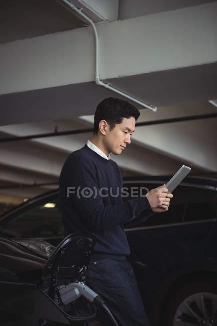 Homme à l'aide de tablette numérique lors du chargement de la voiture électrique dans garage — Photo de stock