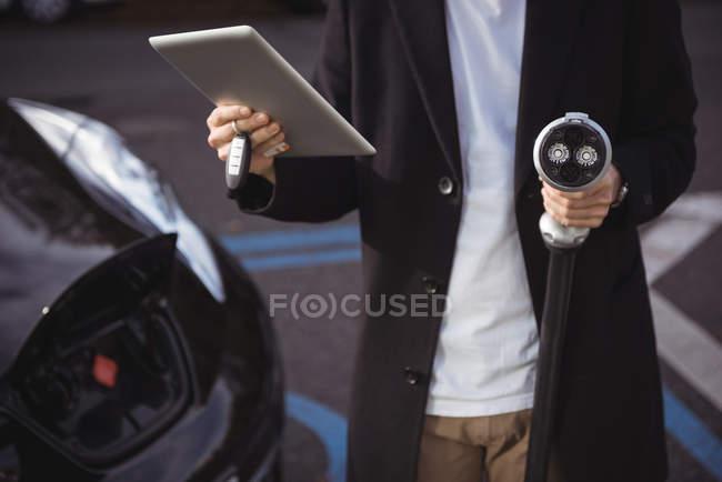 Mittleren Bereich des Mannes mit digital-Tablette im Elektrofahrzeug Ladestation mit gedrückter Kfz-Ladegerät — Stockfoto