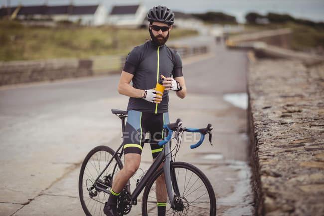 Спортсмен освежается от бутылки во время езды на велосипеде по дороге — стоковое фото