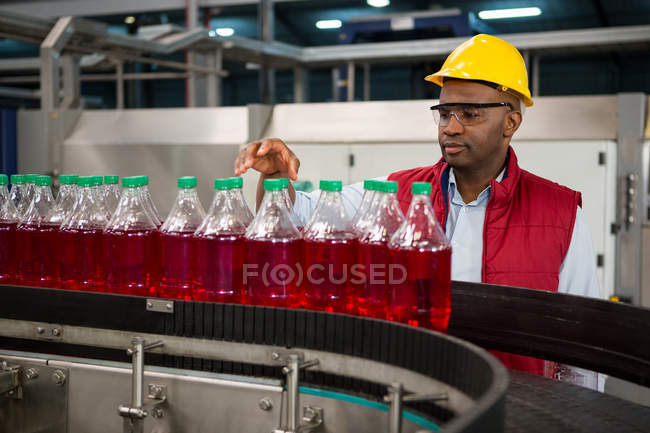 Confident male employee inspecting bottles in juice factory — Stock Photo