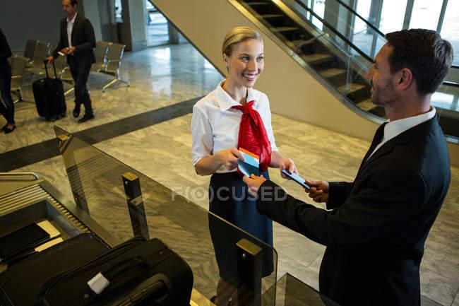 Funcionários do sexo femininos, entregar o cartão de embarque e o passaporte no terminal do Aeroporto — Fotografia de Stock