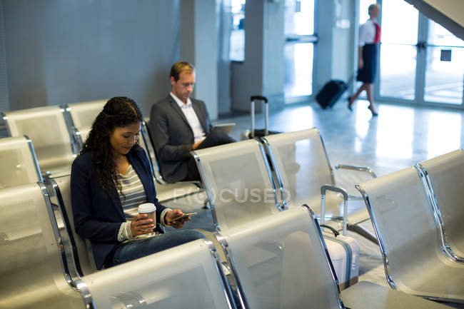 Commuter using mobile phone in waiting area at airport terminal — Stock Photo