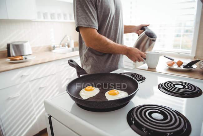 Ovos fritos em uma frigideira na cozinha enquanto homem derramar café na xícara — Fotografia de Stock