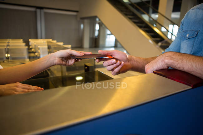 Close-up of female staff giving boarding pass at the check-in desk — Stock Photo