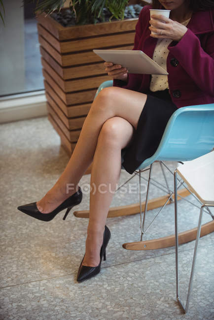 Low section of businesswoman using digital tablet while having coffee in cafe — Stock Photo