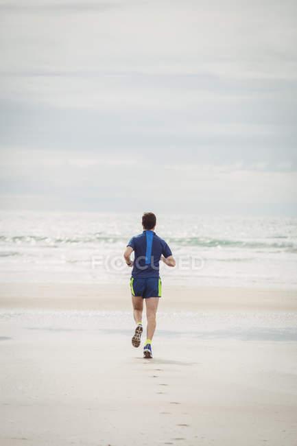 Vista posteriore dell'atleta che corre sulla spiaggia — Foto stock