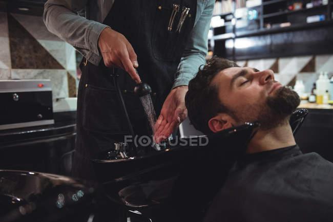 Homme se faire laver les cheveux dans le salon de coiffure — Photo de stock