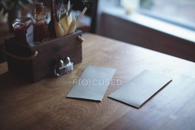 Envelopes on cafe table with sauce tray at cafe — Stock Photo