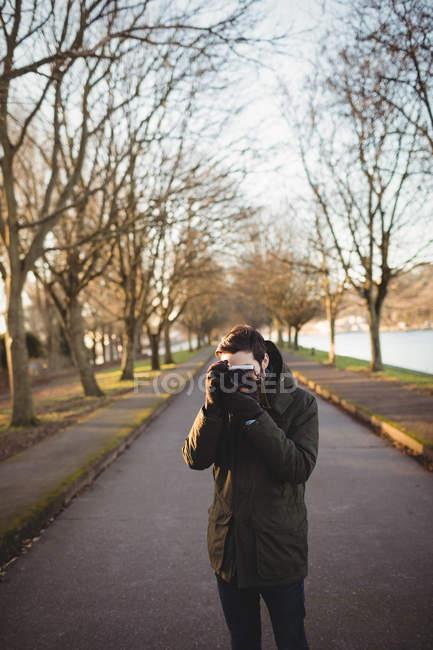Man taking photo on camera near riverside — Stock Photo