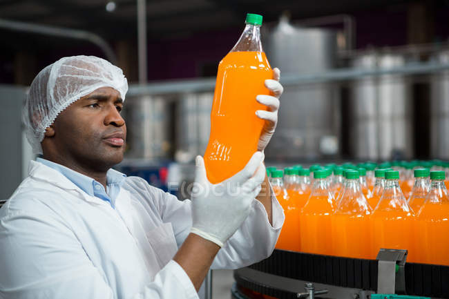 Serious male worker checking products in juice factory — Stock Photo