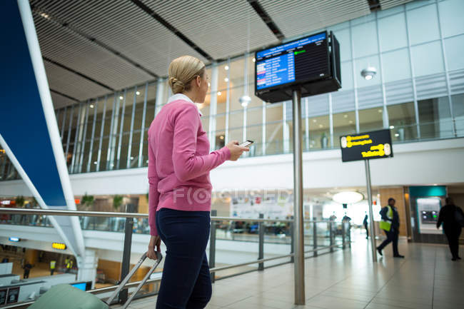 Rear view of female commuter standing with luggage at waiting area in airport — Stock Photo