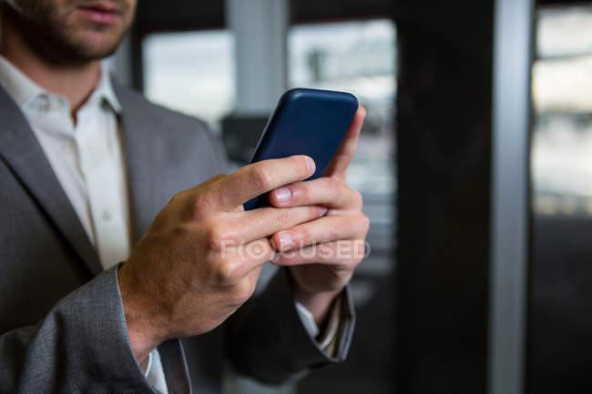 Sección media del hombre de negocios usando su teléfono móvil en la terminal del aeropuerto - foto de stock
