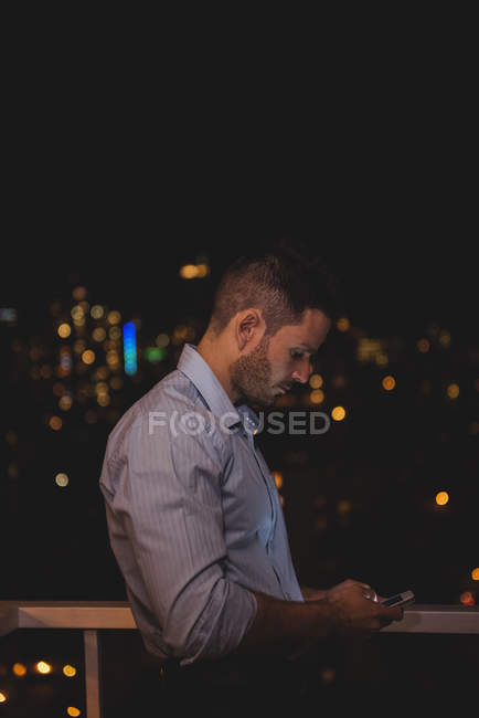 Людина, використовуючи свій мобільний телефон на балконі вночі — стокове фото