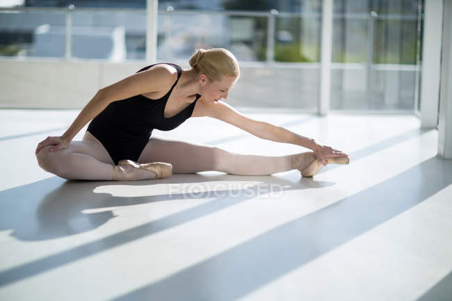 Ballerina performing split in bright studio — Stock Photo
