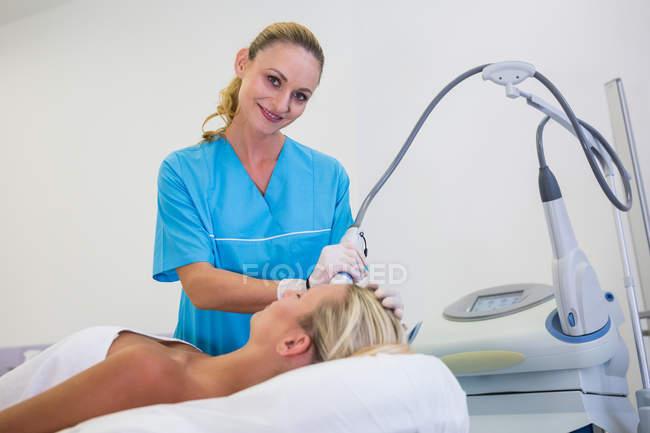 Frau erhält im Schönheitssalon Laser-Epilation auf der Stirn — Stockfoto