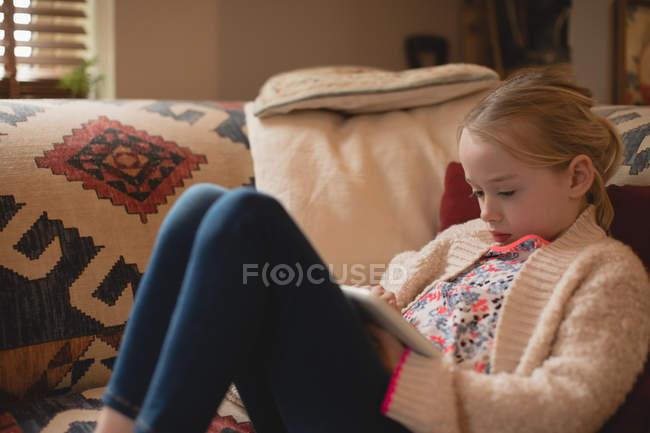 Fille assise sur le canapé et en utilisant une tablette numérique dans le salon à la maison — Photo de stock