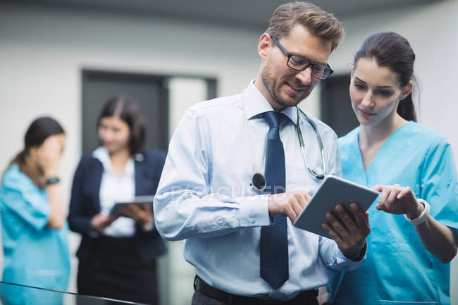 Médico y enfermera discutiendo sobre tableta digital en pasillo de hospital - foto de stock