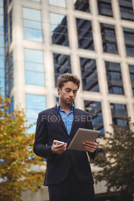 Businessman holding mobile phone and using digital tablet on street — Stock Photo