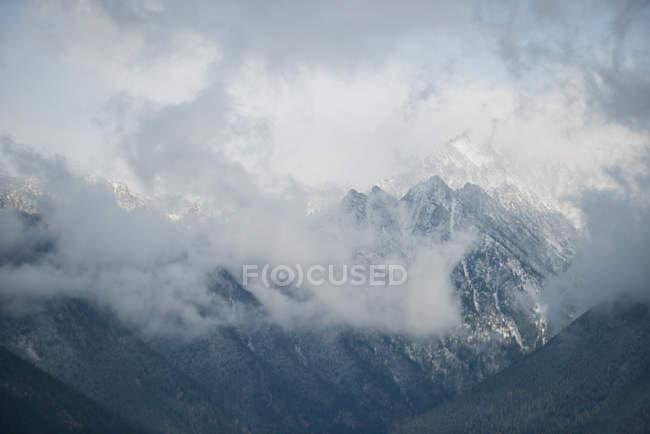 Живописный вид на красивые заснеженные горы и облака — стоковое фото