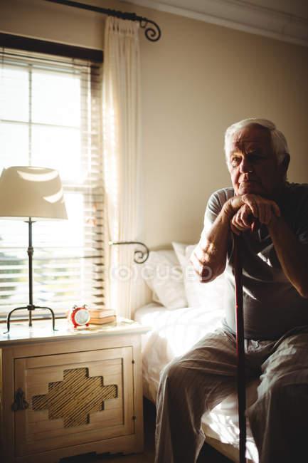 Homme âgé réfléchi avec son bâton de marche dans la chambre à coucher à la maison — Photo de stock